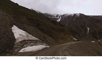 Driving Through Mountainous Terrain - Wideshot as the car...