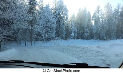 Driving through the winter forest on snowy road