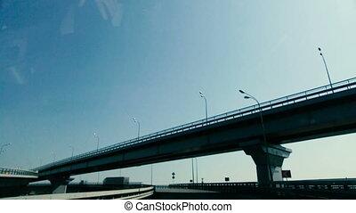 Driving car goes under an overpass.