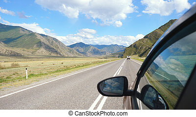 Driving view from side of car mirror mountain valley. Beautiful landscape of a road in the mountains on sunny day