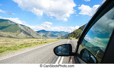 Driving view from side of car mirror mountain valley. Beautiful landscape of a road in the mountains on a sunny day with clouds in the sky