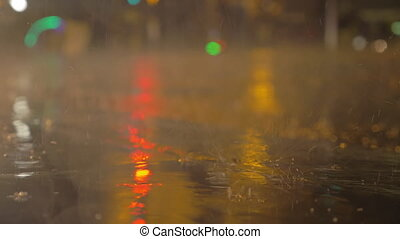 Slow motion close-up shot of raindrops falling into puddle in the street in the evening. City and car lights reflecting in water and wet asphalt. Autumn drizzle
