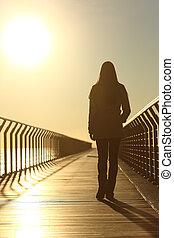 droevige vrouw, silhouette, wandelende, alleen, op, ondergaande zon