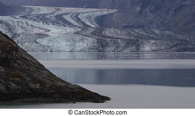 Drone Aerial from Glacier Bay Alaska. Clacier front revealing it self behind mountain in Glacer Bay National Park.