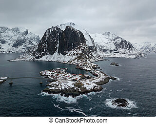 Drone aerial top view of Lofoten Islands in Norway. Winter Landscape with traditional wooden red fisherman huts and this beautiful Mountain in the background. Winter travel destination.