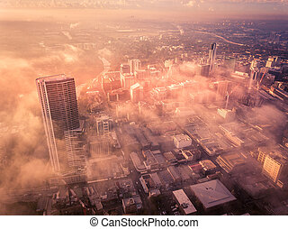 Drone aerial view of a misty foggy morning in a bustling downtown central business district