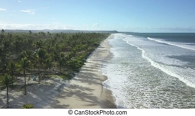 Drone aerial view of waves break on white sand beach. ...