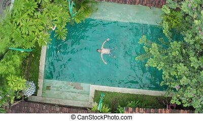 Drone aerial view of Young man floating over blue swimming...