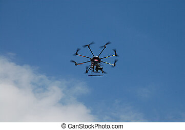 Aircraft type Dron photographed from the ground in flight and shooting events below it.
