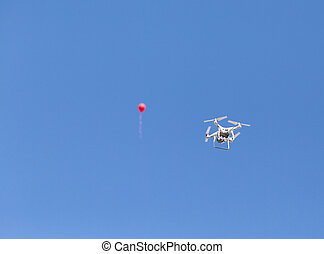 Drone and balloon on blue sky
