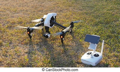 Drone and controller stands on grass - Drone and controller...
