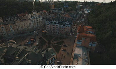 Drone Camera Moves under Roofs of Buildings on the Old Narrow European Streets with Colorful Houses and Pedestrians at Sunset 4K