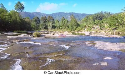 drone flies above flat river stones to girl