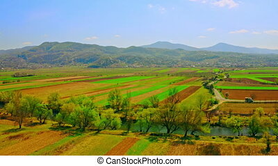aerial view on agricultural fields and river on the background mountains landscape in spring season