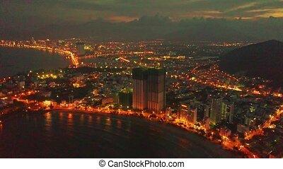 Drone Flies above Skyscraper in Night Resort City on Shore