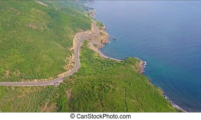 Drone Flies from Ocean Coast along Highway and above Hills