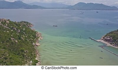 Drone Flies from Rocky Coast of Peninsula Tip to Azure Ocean...