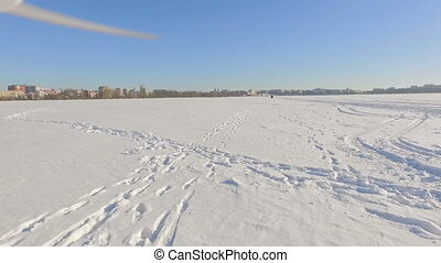 drone flies over a frozen lake near a city park in the background of a winter city in clear sunny weather