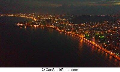 Drone Flies over Dark Ocean Bay by City at Night