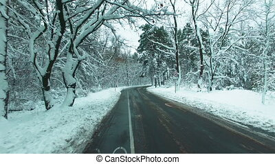 Drone flies over the road through the winter snow forest . Car POV.