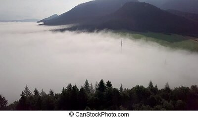 Drone flies over white clouds and forest in the Slovak Tatras