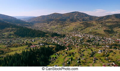 drone flight over forest and buildings in Carpathians -...