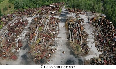 Aerial shot of rusty scrap dump with radioactive iron trash used in liquidation of Chernobyl accident. Drone view of metal garbage on landfill in exclusion zone