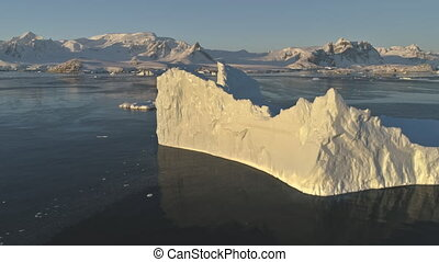 Drone flight over sunlit iceberg. Antarctica. - Close-up...