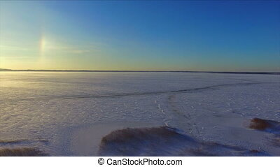 Drone flight over the snowy frozen lake