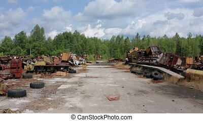 Aerial view of asphalt road and car dump in Chernobyl zone, radioactive metal garbage, wrecked rusty car cabs, wheels, iron change houses abandoned after liquidation of accident at nuclear power plant