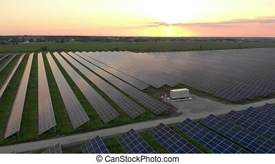 Aerial view of Solar Power Station. Renewable green energy and electrical technology. Field of Solar Panels Stands in a Row in the Fields for Power Production at Sunny day. Green energy concept.