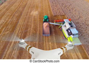 Drone flying above combine harvester