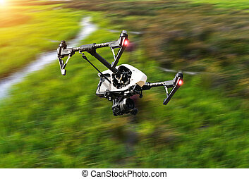 Drone flying above green field