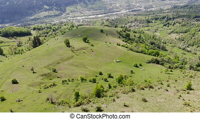 Drone flying above green valley and village, aerial view of...