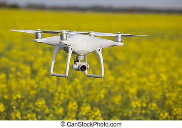 Drone flying above yellow flowers of rapeseed in springtime
