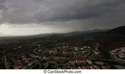 Drone flying and descending over town, view to cottages and...
