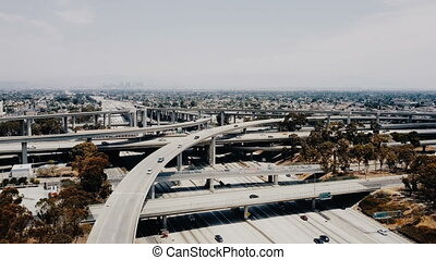 Drone flying around amazing highway junction interchange in Los Angeles with many road flyovers. Incredible cinematic aerial panorama of majestic American Judge Pregerson freeway intersection.