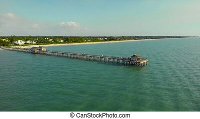 Drone flying around the orbit. Flying along a wooden long pier at sunset time. Sunset over horizon and wooden pier of caribbean beach of Naples in Florida. Travel Naples Beaches Florida, aerial view.