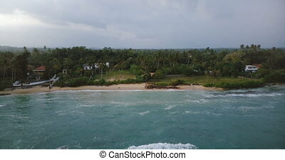 Drone flying backwards above beautiful exotic sea shore with tropical trees and houses, revealing big foaming waves.