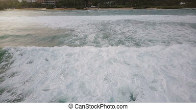 Drone flying backwards from peaceful ocean coastline revealing big foaming waves washing the shore on a sunny summer day