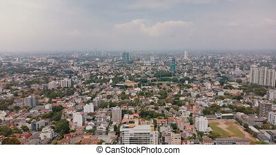 Drone flying backwards high above city of Colombo, Sri Lanka. Aerial panoramic view of amazing Asian cityscape skyline.