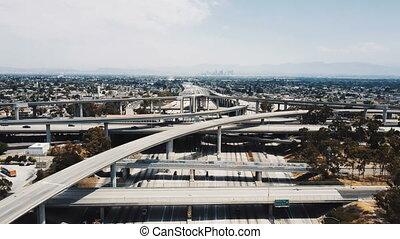 Drone flying backwards over large highway interchange in Los...