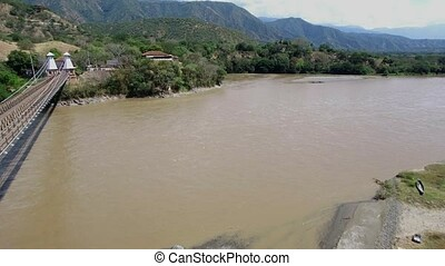 Drone flying backwards over the Puente de Occidente in...