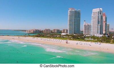 Surfers ride surfs in the ocean waves. Miami Beach