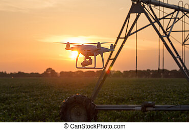 Drone flying in front of irrigation system in field at sunset