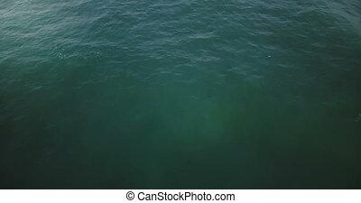 Drone flying low over high foaming waves in open ocean....