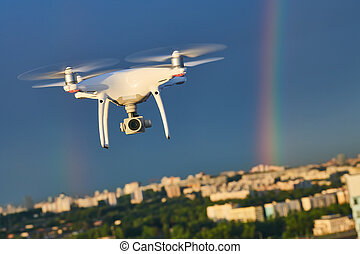 drone flying over city with digital camera at rainbow