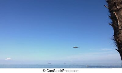 Drone flying over sea. Small drone hovering in a bright blue sky.