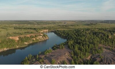 Drone flying over small lake surrounded by sparse vegetation with blue skies and white clouds