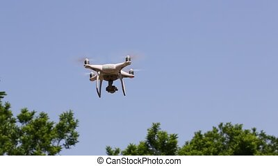 Drone flying with clear blue sky with tree